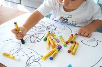 Ребенок рисует карандашами разные фигуры и разукрашивает их
